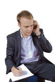 Young businessman on the phone taking notes Royalty Free Stock Photography
