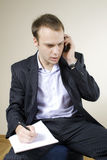Young businessman on the phone taking notes Stock Images