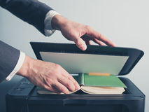 Young businessman photo copying a book. The hands of a young businessman is placeing a book on a flatbed scanner in preperation for copying it Royalty Free Stock Image