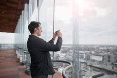 Young businessman photographing a city on the phone with a skyscraper. Royalty Free Stock Photos