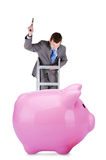Young businessman and piggy bank. Young businessman going to  break the piggy bank isolated on white background Stock Photo