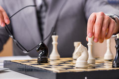 The young businessman playing chess in the office Stock Image