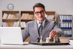 The young businessman playing chess in the office Royalty Free Stock Photography