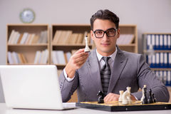 The young businessman playing chess in the office Stock Photos