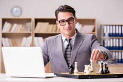 The young businessman playing chess in the office Stock Photo