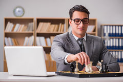 The young businessman playing chess in the office Royalty Free Stock Photo