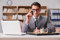 The young businessman playing chess in the office Royalty Free Stock Photos