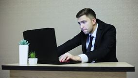 Young businessman playing a computer game at work. An employee sits back while working stock video