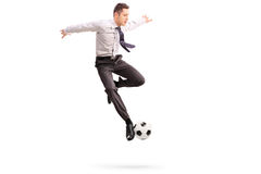 Young businessman playing football Royalty Free Stock Image