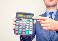 Young businessman pointing on calculator.Five Stars Sign. Taxes Stock Image