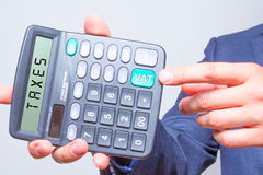 Young businessman pointing on calculator. Vat Sign. Taxes busine Royalty Free Stock Photo