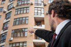 Young businessman pointing in direction of apartment. Stock Photo