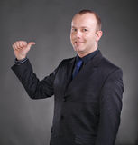 Young businessman pointing at himself. Portrait of a happy young businessman pointing at himself on a gray background stock images