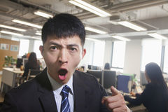 Young Businessman pointing and shouting, looking at camera Royalty Free Stock Images