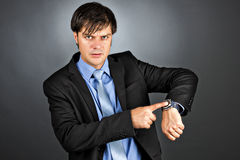 Young businessman pointing to his watch with an angry expression Stock Images