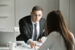 Young businessman is pointing to a mistake in a paper. Young handsome businessman is pointing to a mistake in a paper, incorrectly done task by a women or she is Stock Photo