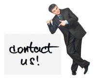 Young businessman points on a card Contact Us on a white. Background Stock Photo
