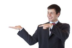 Young businessman points to blank ad space at palm Stock Photo