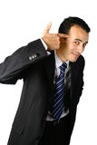 Young businessman points to his temple. In gesture of thinking, isolated stock photo
