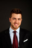 Young businessman portrait on a dark background Stock Photos