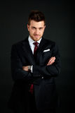 Young businessman portrait on a dark background. Elegant young businessman with a red tie on a dark background Royalty Free Stock Image