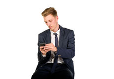 Young businessman portrait isolated. Young businessman sitting and watching to smart phone Stock Images