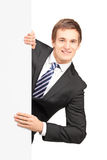 Young businessman posing behind a blank panel. Isolated on white background Royalty Free Stock Photo