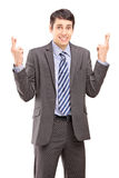 Young businessman posing with fingers crossed for luck Stock Photos