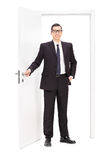 Young businessman posing in front of a door Stock Photography