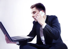Young businessman posing with laptop and phone. Stock Photo