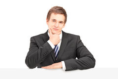 Young businessman posing with a panel. Young businessman posing with a blank panel  on white background Stock Image