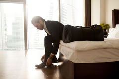 Young businessman preparing to business trip. Man with luggage puts on shoes on hotel room bed. Young businessman getting ready to go on business trip Royalty Free Stock Photography
