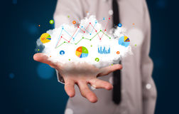 Young businessman presenting cloud with charts and graph icons a Stock Images