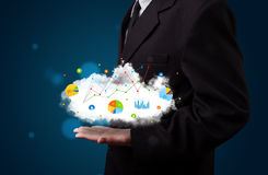 Young businessman presenting cloud with charts and graph icons a Royalty Free Stock Images