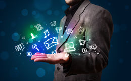 Young businessman presenting colorful glowing social media icons Royalty Free Stock Photography