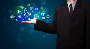 Young businessman presenting colorful glowing social media icons Stock Photo