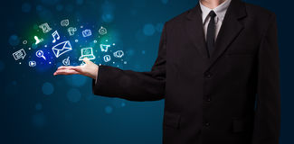 Young businessman presenting colorful glowing social media icons Stock Image