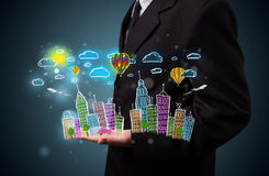 Young businessman presenting colorful hand drawn metropolitan ci Royalty Free Stock Images