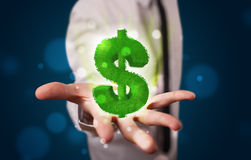 Young businessman presenting green glowing dollar sign Stock Images