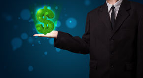Young businessman presenting green glowing dollar sign Stock Photos