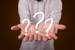 Young businessman presenting hand drawn question marks Royalty Free Stock Photo