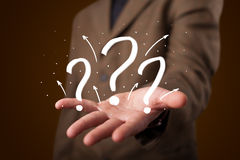 Young businessman presenting hand drawn question marks Stock Photos