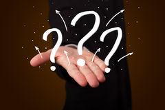 Young businessman presenting hand drawn question marks Stock Photo