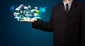 Young businessman presenting magical clouds with letters and bal Stock Images