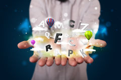 Young businessman presenting magical clouds with letters and bal Royalty Free Stock Photo