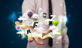 Young businessman presenting magical clouds with letters and bal Royalty Free Stock Photos