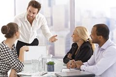 Young businessman presenting to partners. In meetingroom Royalty Free Stock Images