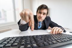 Young businessman is pressing enter key on keyboard and submitting a form Stock Photos