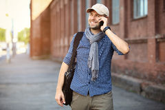 Young businessman professional on smartphone walking in street using app texting sms message on smartphone Stock Image