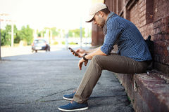 Young businessman professional on smartphone walking in street using app texting sms message on smartphone Stock Images